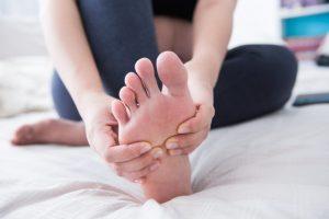 足の甲をマッサージしている女性