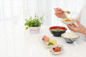 バランスの取れた和食の朝食を食べている女性