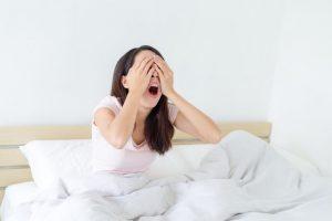 眠そうに目元を押さえる寝起きの女性
