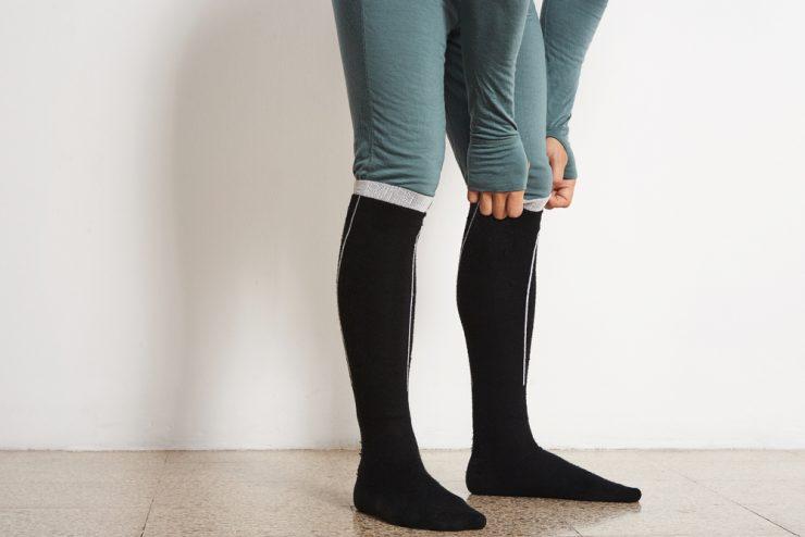 ズボンのすそをひっぱっている女性の下半身