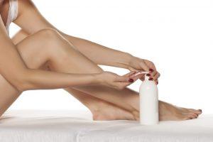 クリームを出している女性の手と足が移っている写真