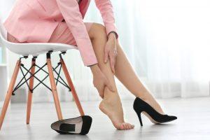 ハイヒールのせいでむくんだ脚をマッサージをしている女性