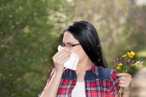 花粉のせいで鼻水が止まらない女性