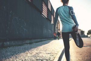 準備運動として足を伸ばしている女性ランナー