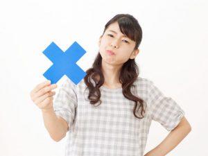 青いバツマークを持っている女性