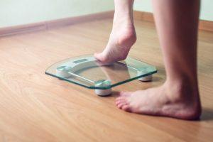 体重計に乗ろうとしている女性