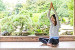 日本庭園を背にヨガをしている女性
