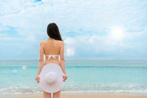 砂浜に立つ白い水着を着た女性
