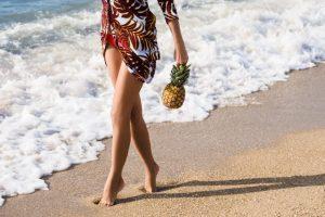 パイナップルを持って海岸線を散歩する女性