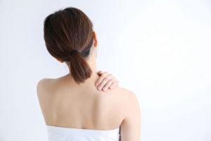 肩を触っている女性の後ろ姿