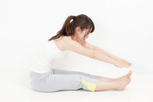 脚を伸ばし上半身を倒すストレッチをしている女性