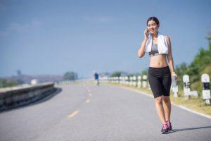 ランニング後汗を吹きながら歩いている女性