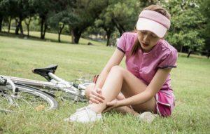 自転車の横で足を抱えている女性