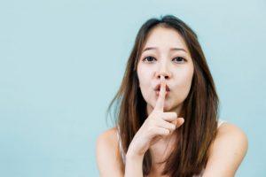 指を口に当てて静かにするように指示している女性