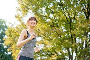 新緑の中ペットボトル片手にランニングをする女性