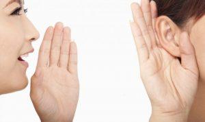 女性が手を口に当ててと何の人に何かを言う