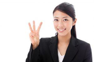 人差し指と中指と薬指を立てている女性