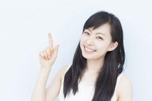思わず見てるこちらも笑顔になってしまうような愛くるしい笑顔で指を使い方向を示している女性