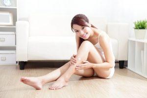 無駄毛のない綺麗な自分の脚を撫でる女性