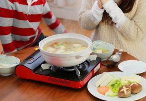 鍋の中の具材に火が通ったので早速食べようとしている女性