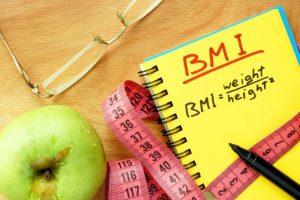 BMIと書かれたノートとメジャーと青りんごとメガネとペン