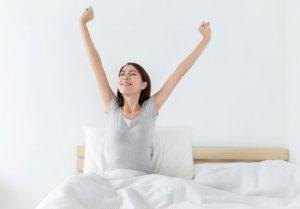 寝起きにグッと伸びをしている女性