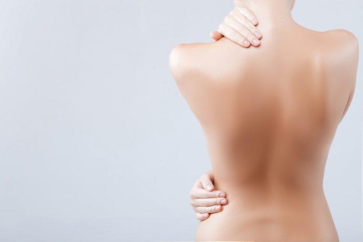背中に手をあてた裸の女性が後ろ向きに立っている