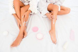 足にクリームを塗っている女性達