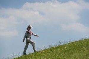 昼の河川敷を散歩している女性