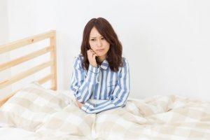 ベッドで渋い顔をしている女性