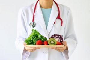野菜が乗ったお盆を持っている男性医師