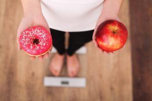 りんごとドーナツを手に持って体重計に乗っている女性