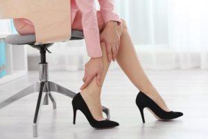 椅子に座ってふくらはぎを触っている女性