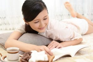ソファーで横たわりながら読書を楽しむ女性