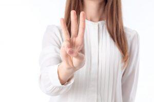 3本指を出している女性