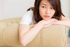重ねた手の上に顎を乗せてソファーに横たわる女性