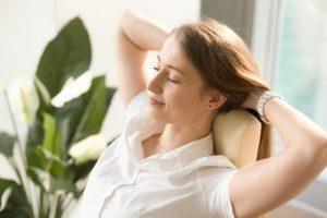 後頭部に手を当ててゆっくりと伸びをしている女性
