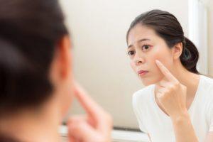 肌荒れが気になり鏡で確認している女性