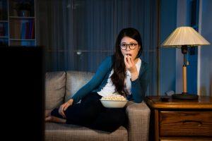 ソファーに座りながらテレビ番組を鑑賞している女性