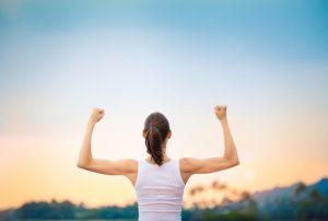 女性が筋肉ムキムキで力こぶを両手で作っている