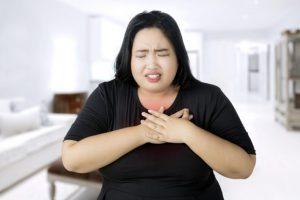 苦しそうな表情で心臓のあたりを両手で押さえている太り気味の女性