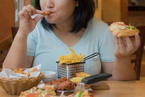フライドポテトやハンバーガーなど脂っこいものばかりを食べている女性
