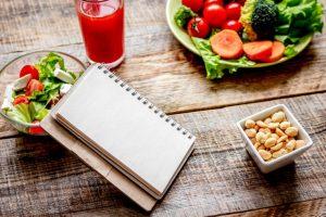 サラダと赤いジュース、ノートが机の上においてある