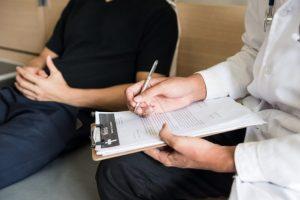 診断結果を記入している医師と患者