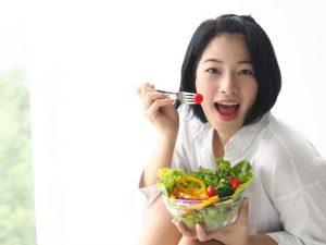 サラダに入っているプチトマトを食べようとしている女性
