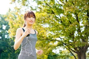 緑が美しい公園をジョギングする女性