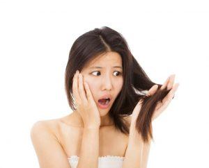 髪を触ってびっくりしている女性