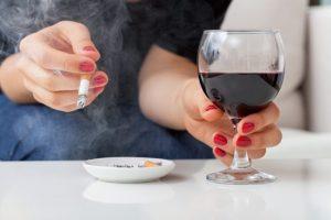 ワインとタバコを持っている人
