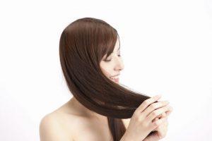 サラサラな自分の髪の手触りを楽しむ女性