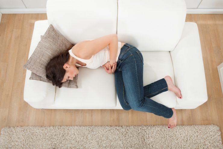 ソファでお腹を抱えてる女性